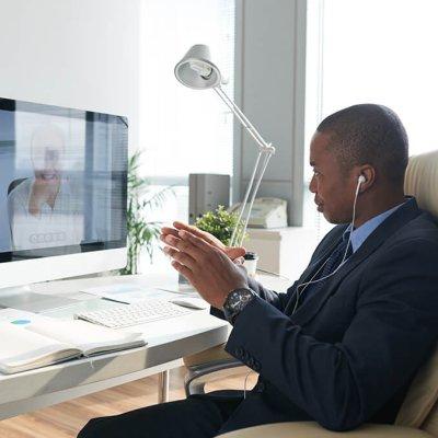 African-American entrepreneur in headphones having video conference with coworker